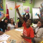 """Elementary students with their adviser from 4-H showing their """"achievements"""" from an origami workshop at Make-It Springfield in 2016."""